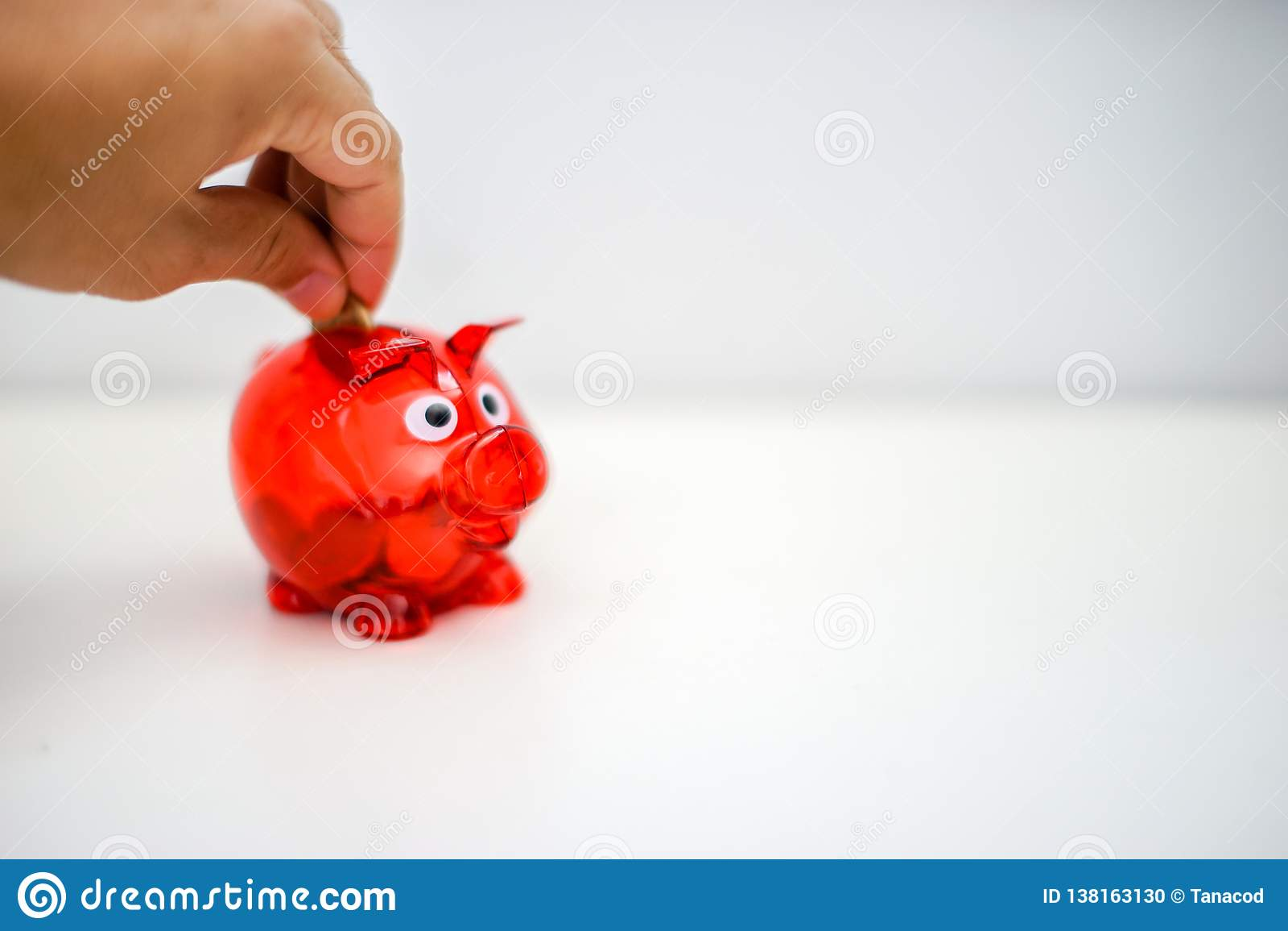 放硬币的亚洲人手入红色存钱罐