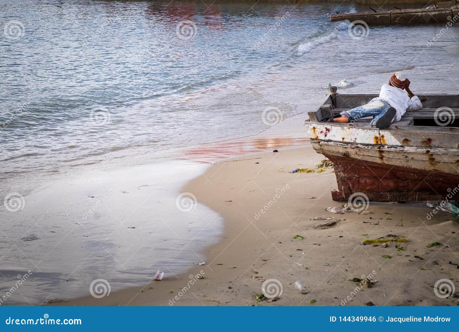放置在小船的一个年轻男孩看来在深刻的想法