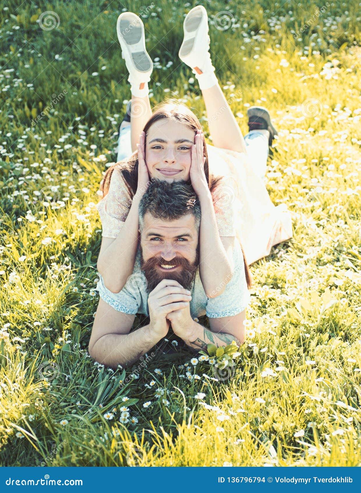 放置在草春日的男人和妇女 春天休闲概念 在放置在草甸,自然的愉快的笑容的夫妇