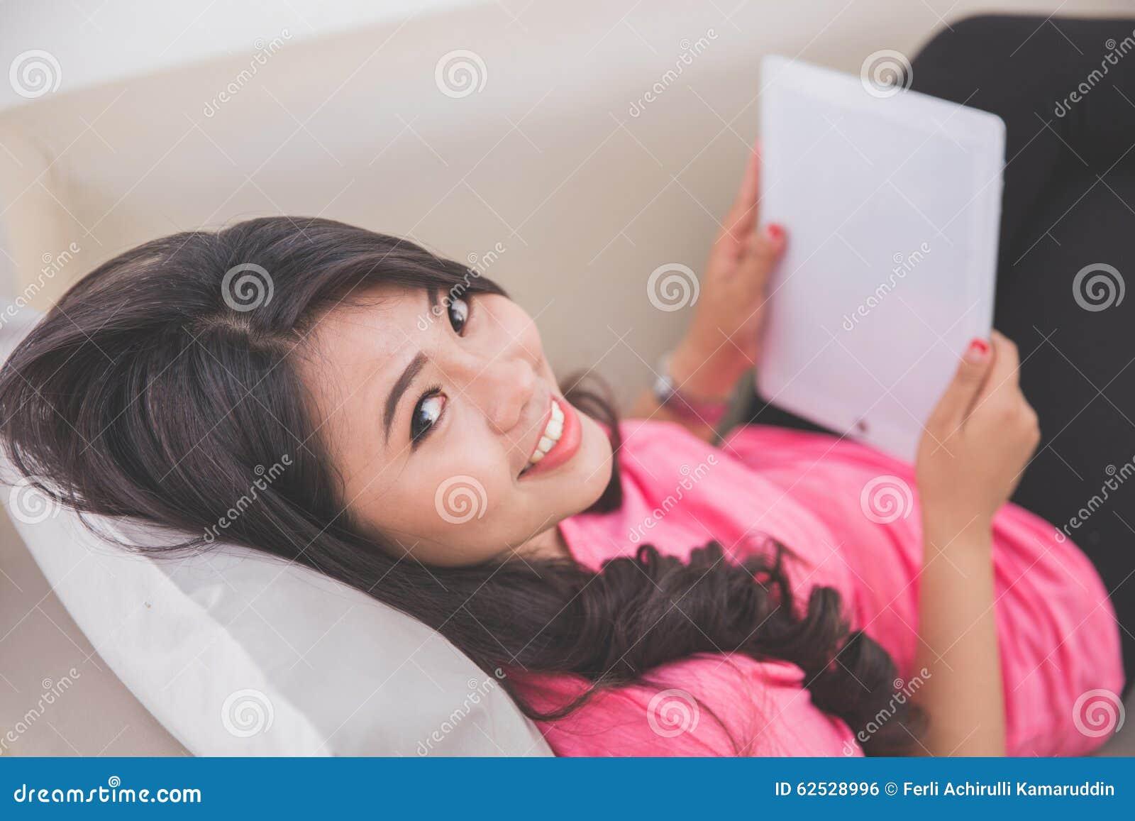 放置在长沙发的妇女使用片剂个人计算机