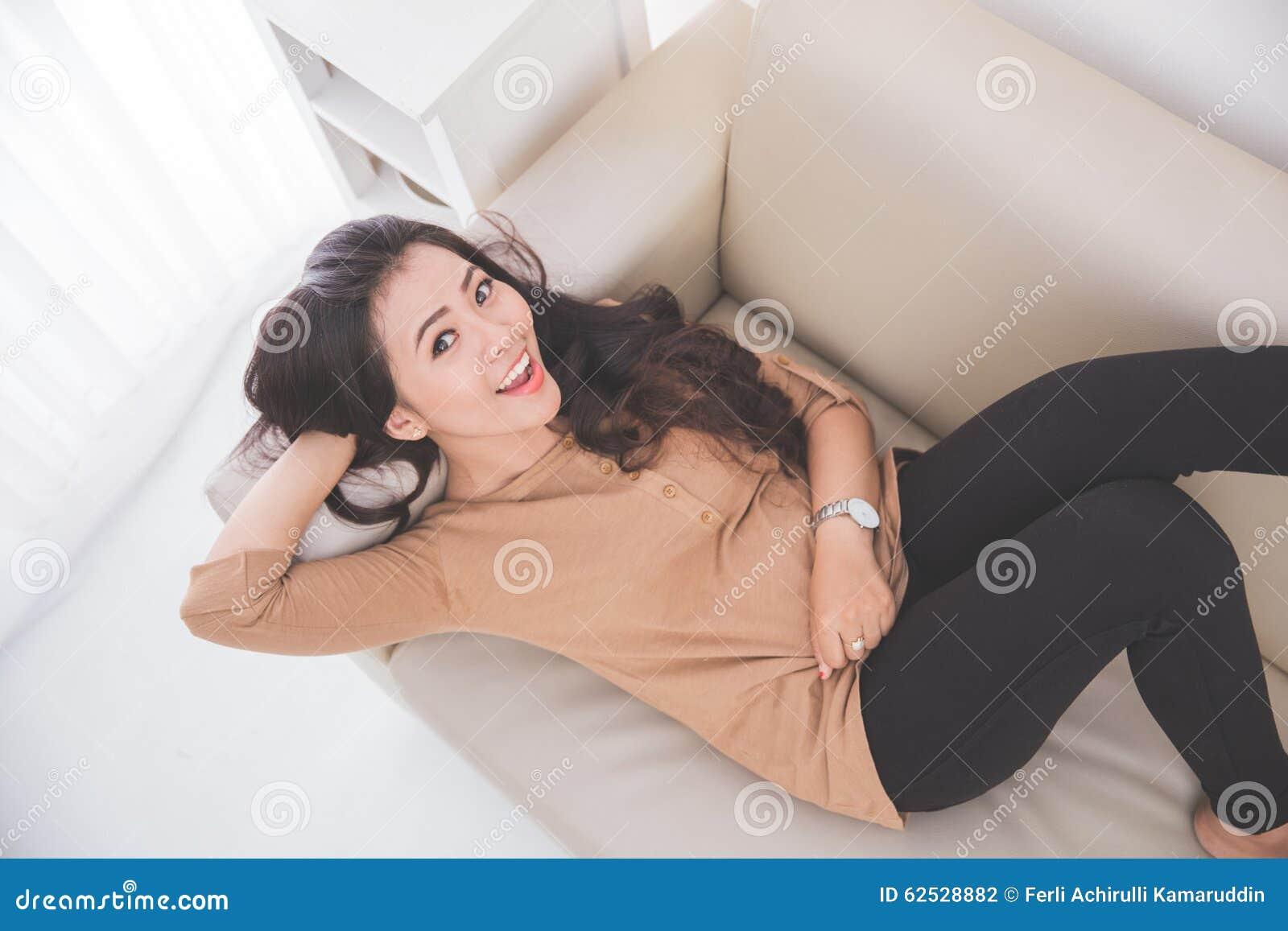 放置在长沙发的妇女,微笑对照相机