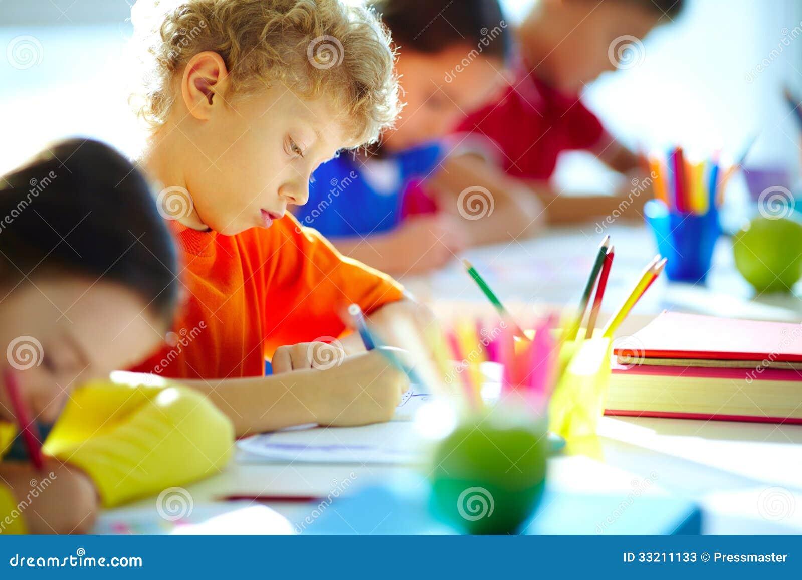 逗人喜爱的男小学生图画画象在工作场所的在他的同学中.