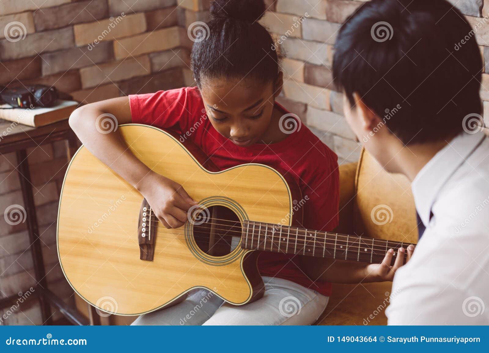 教黑人女孩的男性家庭教师弹吉他