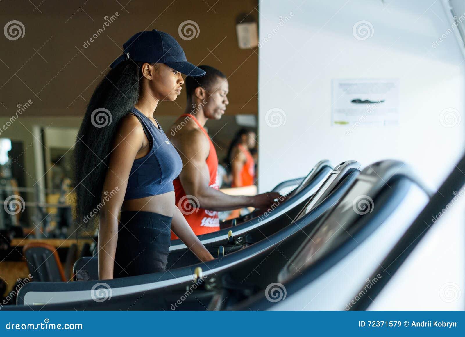 黑教练员和性感的非裔美国人的妇女踏车的在健身房 球概念健身pilates放松