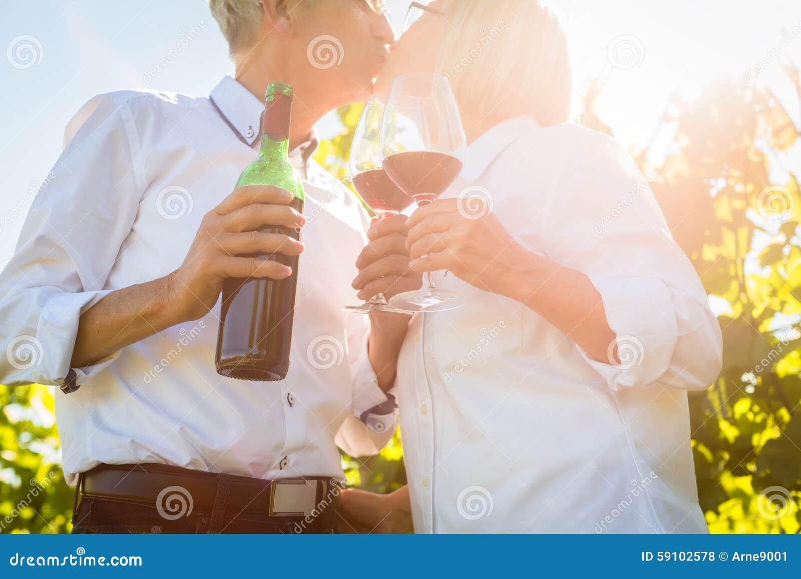 敬酒与酒杯的资深夫妇在葡萄园里