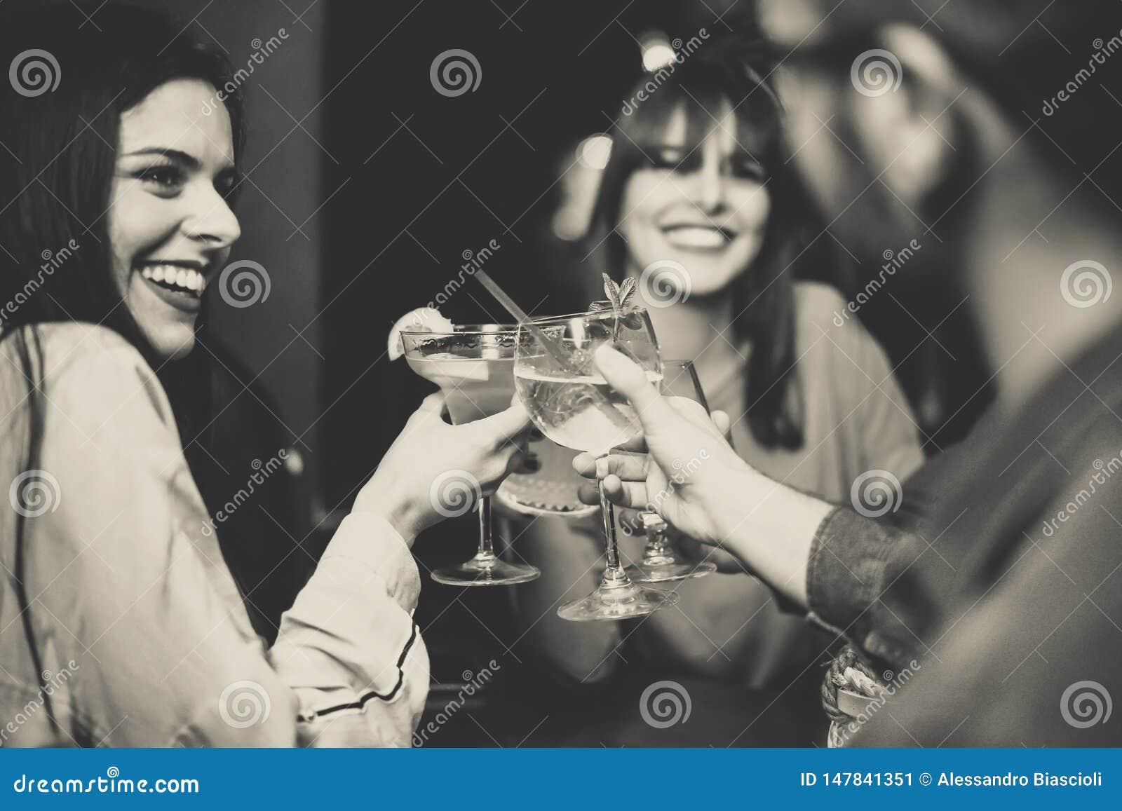 敬酒和欢呼鸡尾酒的愉快的年轻朋友在迪斯科酒吧-获得多种族的人民享受饮料的乐趣在俱乐部
