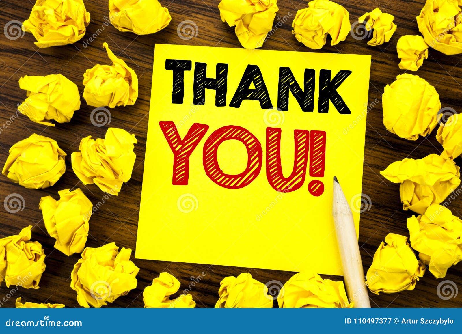 文字文本陈列感谢您 在稠粘的便条纸写的感谢消息的企业概念,与被折叠的ye的木背景