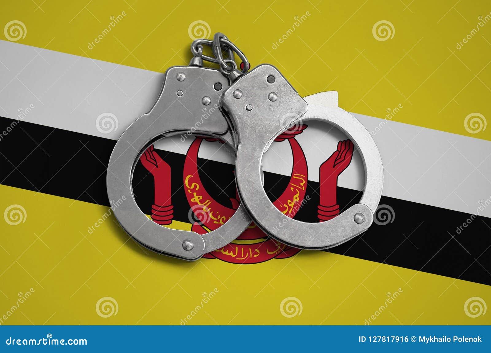 文莱达鲁萨兰旗子和警察手铐 法律在国家和保护的遵守的概念免受罪行