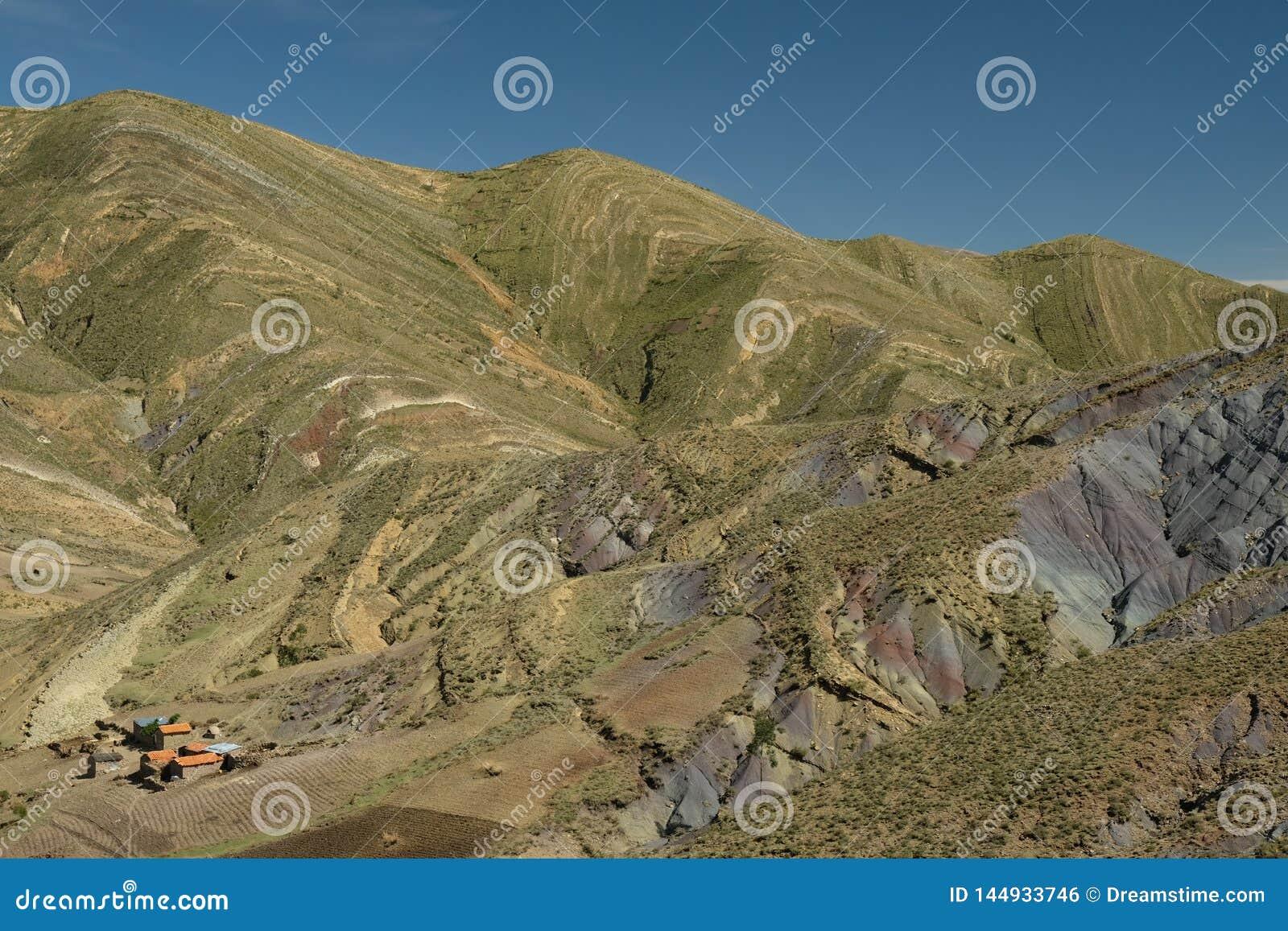 斑纹的绿色和彩虹山在马拉瓜火山口 有农厂房子的玻利维亚
