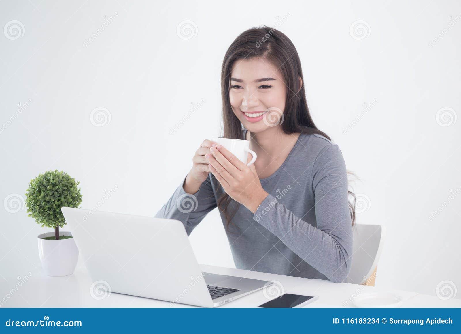 新一代亚洲人女商人坐的和饮用的咖啡