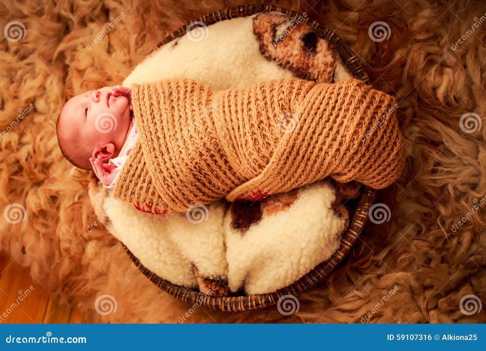 新出生的婴孩在圆的羊毛枕头睡觉