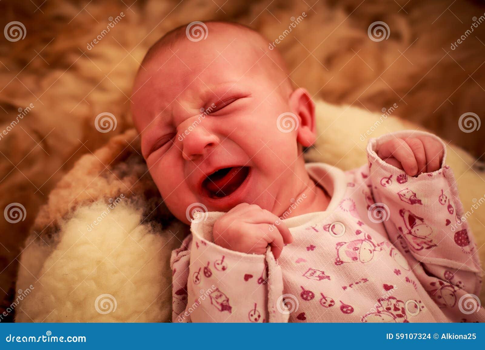 新出生的婴孩在幼稚紧身衣裤的羊毛枕头哭泣