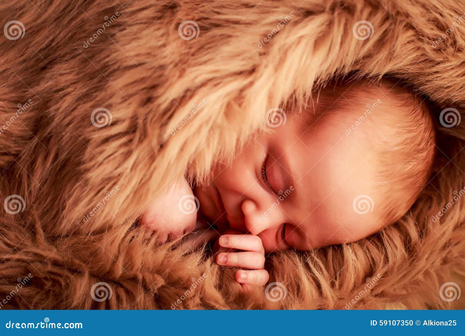 新出生的婴孩睡觉面孔特写镜头画象用在面颊下的手