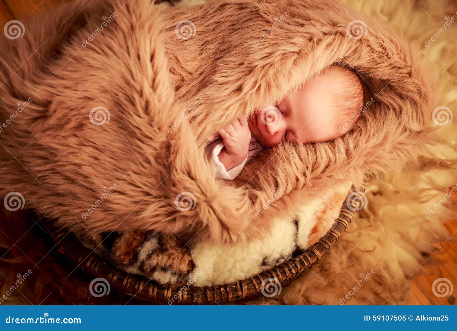 新出生的婴孩睡觉面孔画象用小手