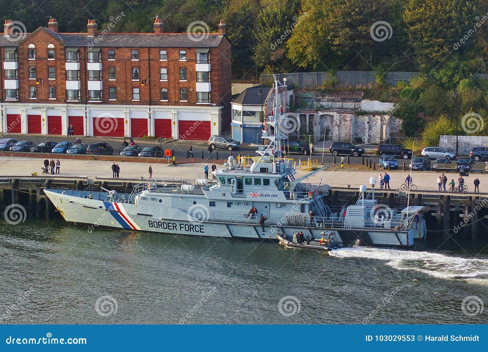 新堡,英国- 2014年10月5日, -她的停泊的英国边界力量切削刀HMC搜寻者与肋骨巡逻艇以后的Al