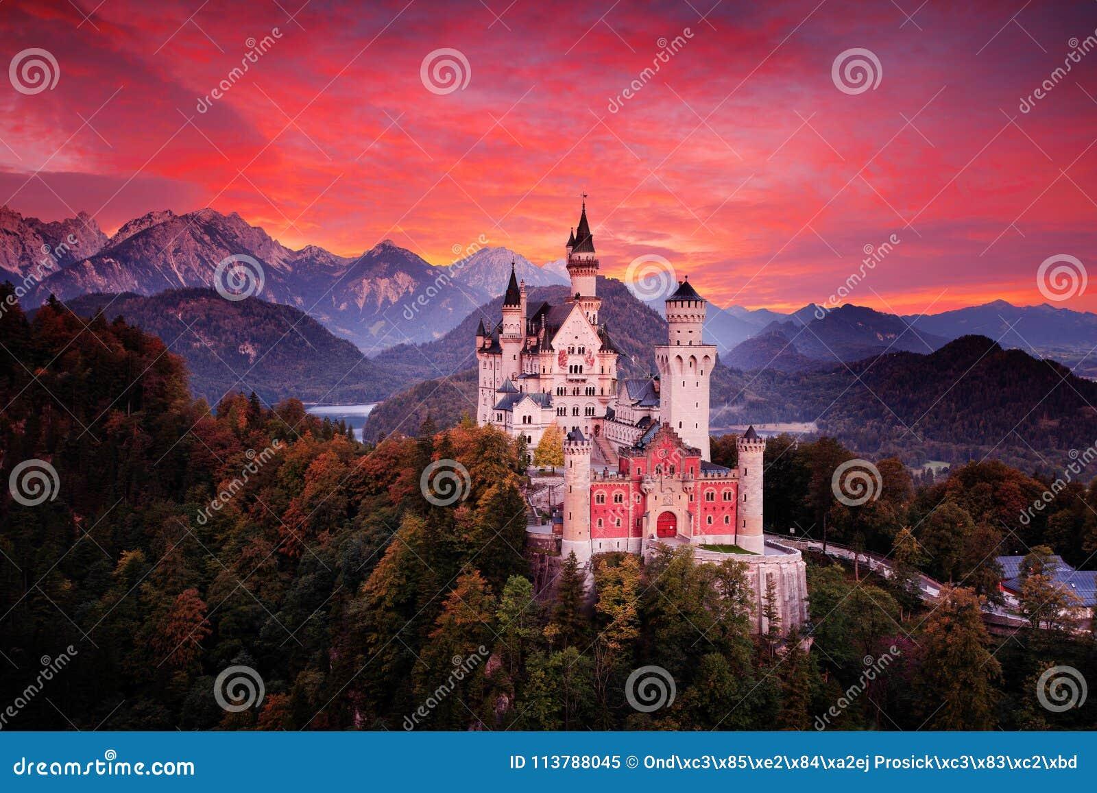 新天鹅堡童话城堡 血淋淋的云彩的美好的日落视图与秋天颜色的在树,暮色夜,巴伐利亚
