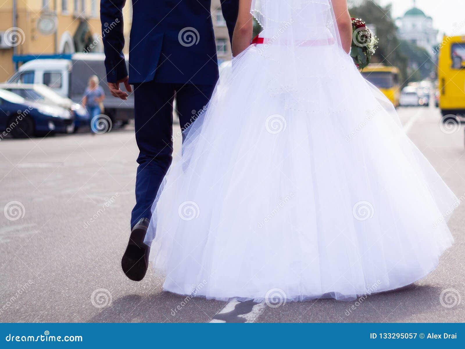 新娘和新郎举行手,当走在路的他们在城市时 详细婚礼