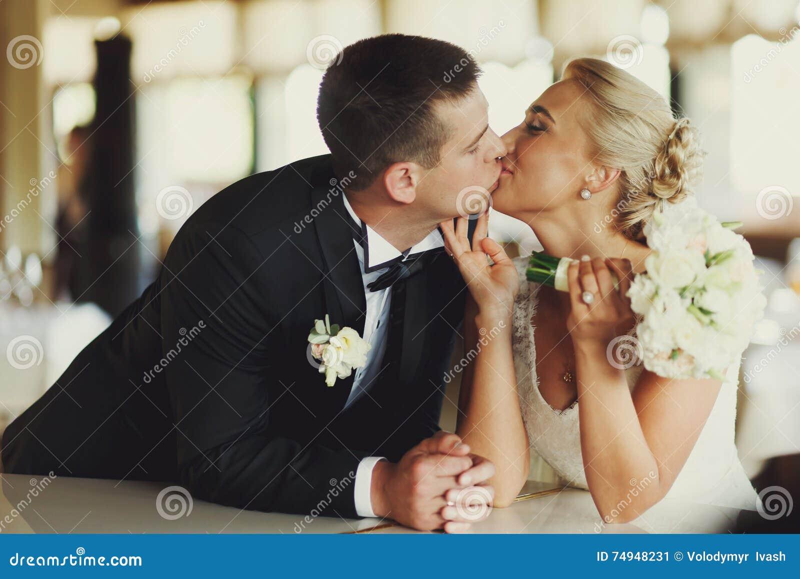 新娘和新郎亲吻倾斜在钢琴