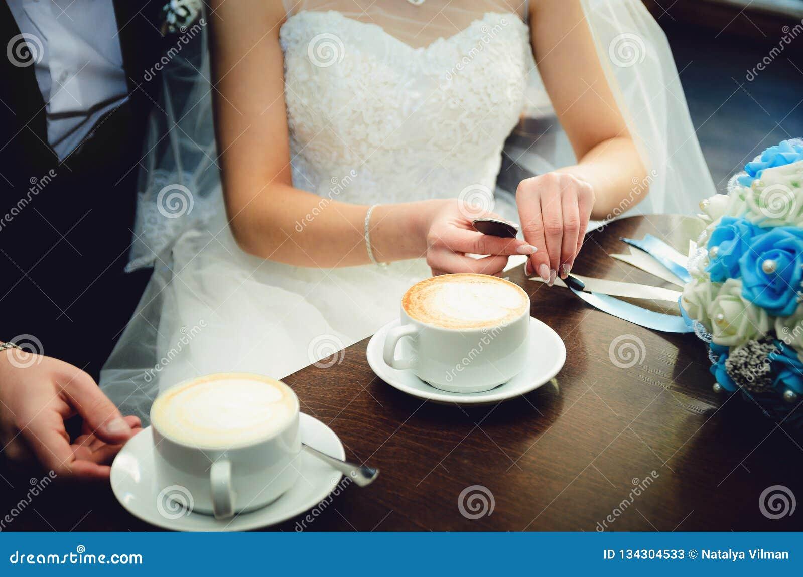 新娘和新郎在他们的婚礼那天,在咖啡馆的饮料咖啡