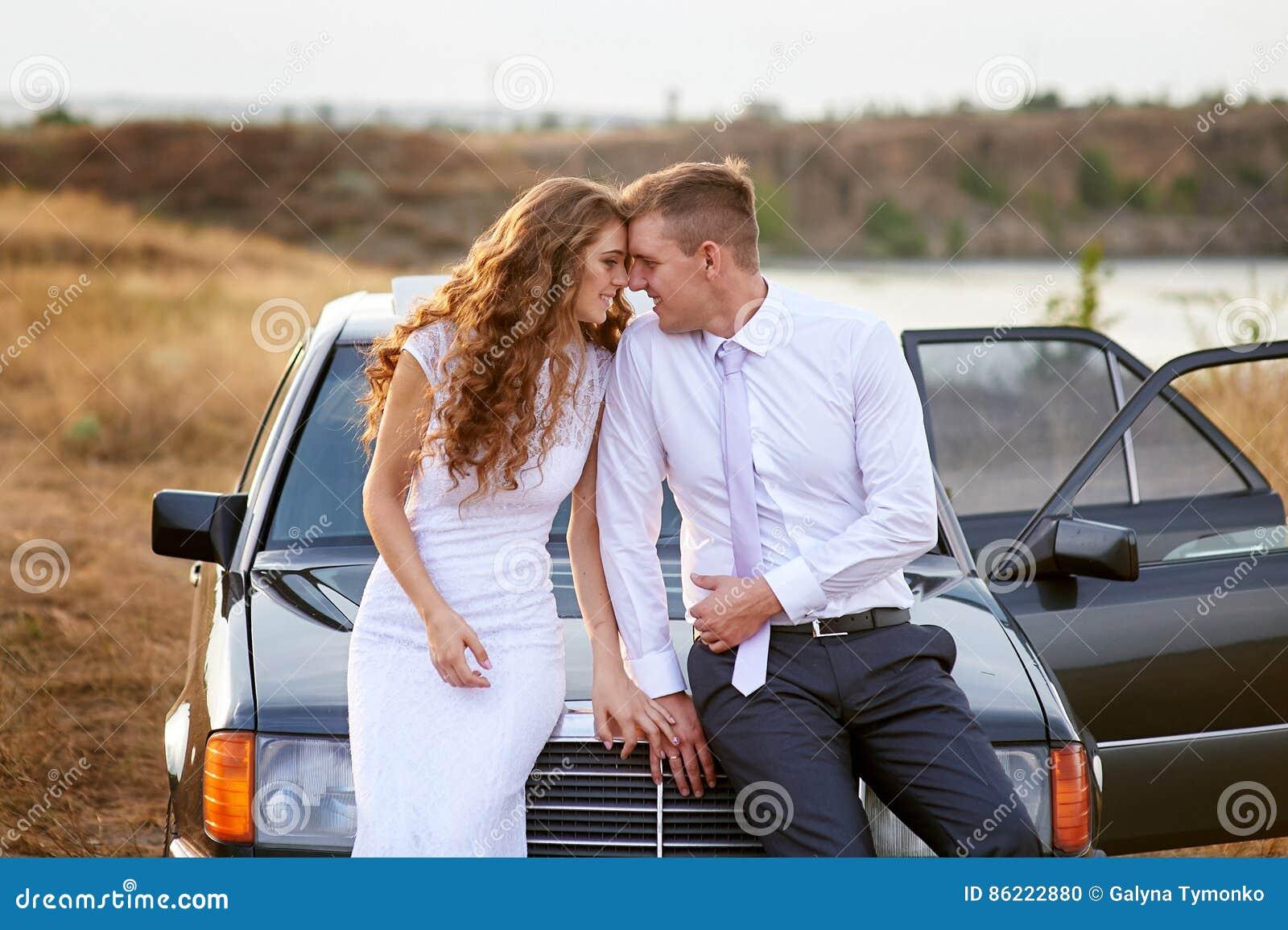 新娘和新郎坐汽车的敞篷