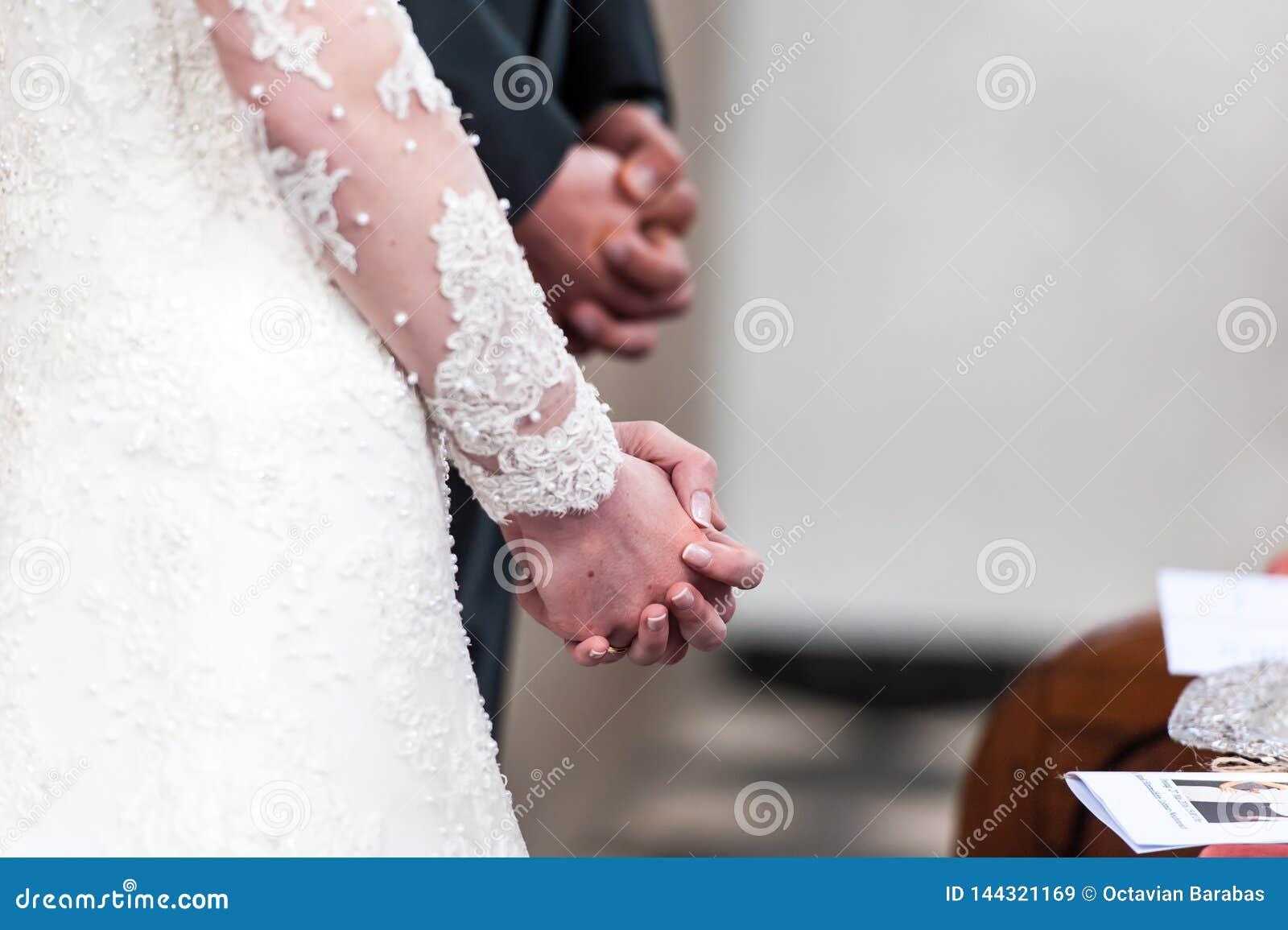 新娘和新郎折叠的手在教会里