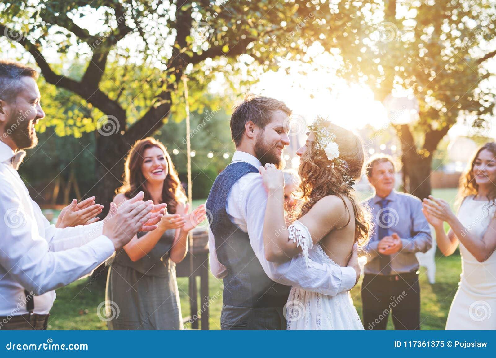 新娘和新郎跳舞在结婚宴会外面在后院