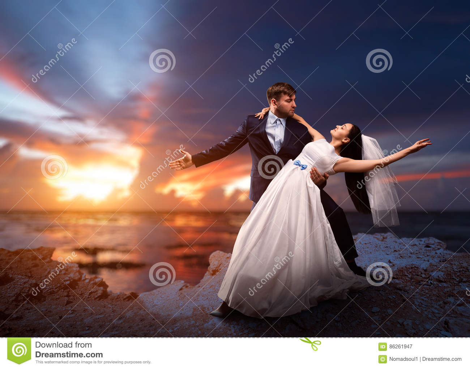 新婚佳偶跳舞,海和日落在背景