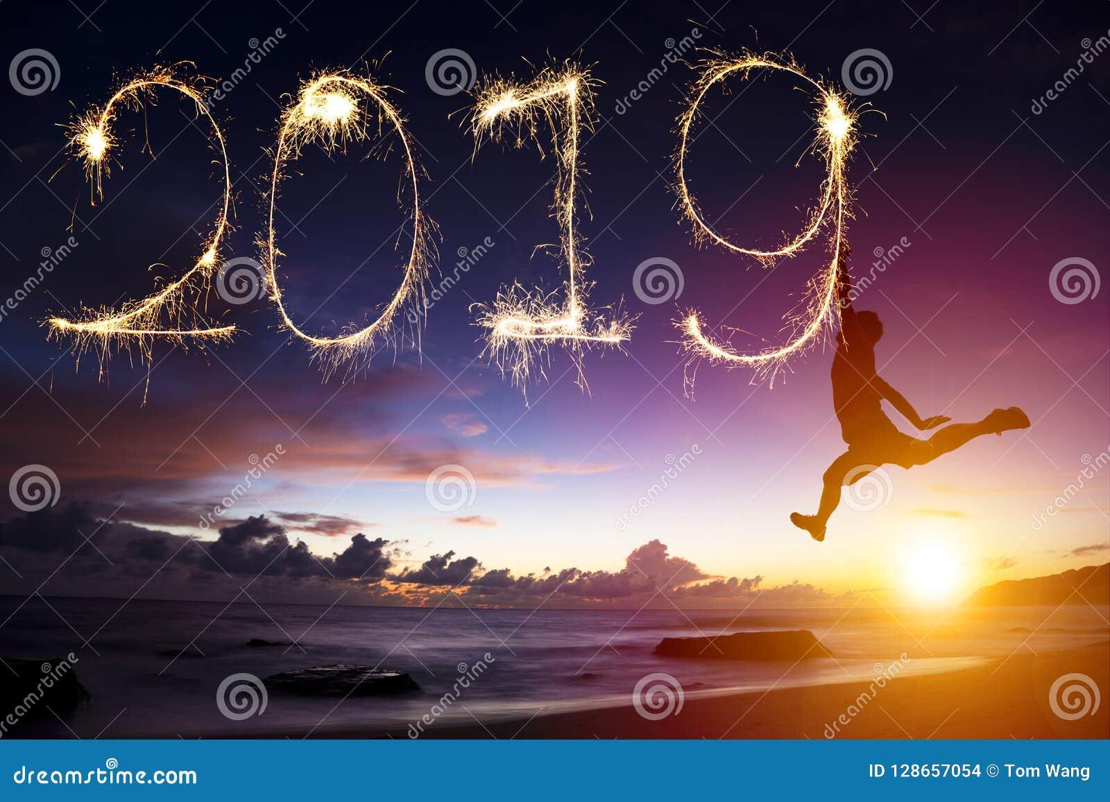 新年2019年 跳和画在海滩的人