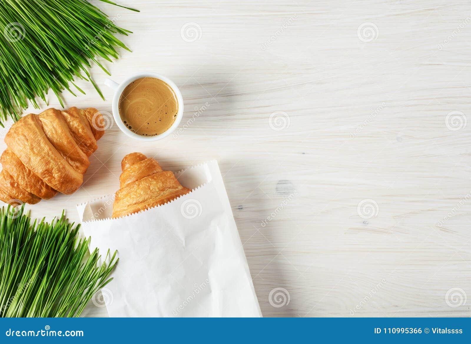 新月形面包、咖啡和发芽的麦子在木背景