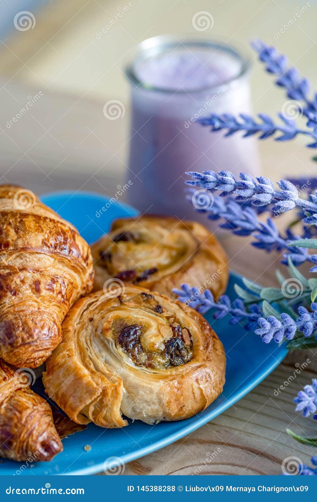 新月形面包、小圆面包用葡萄干在一块蓝色板材和蓝莓酸奶在玻璃瓶子