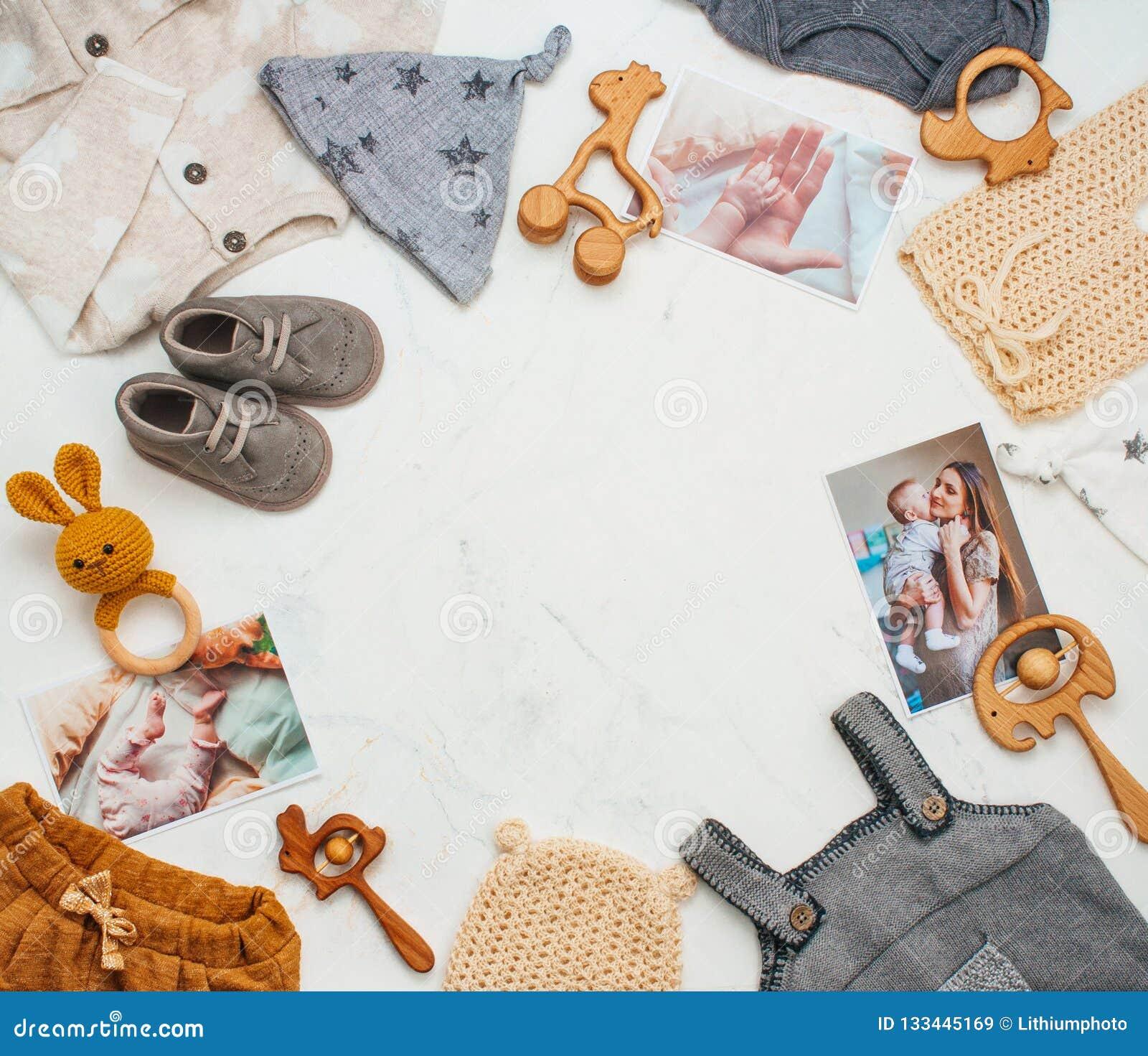新生儿衣物,在轻的大理石背景的玩具框架