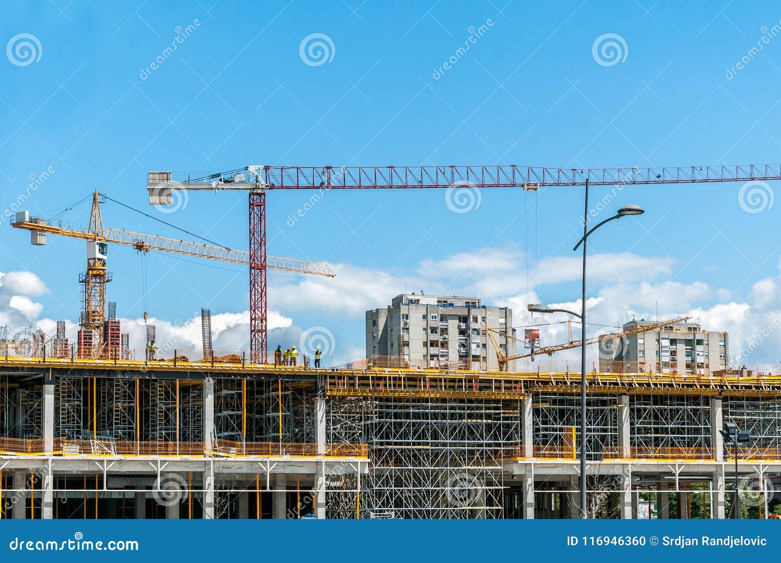 新的购物中心或购物中心建造场所在有起重机的机械,脚手架城市,具体与钢增强