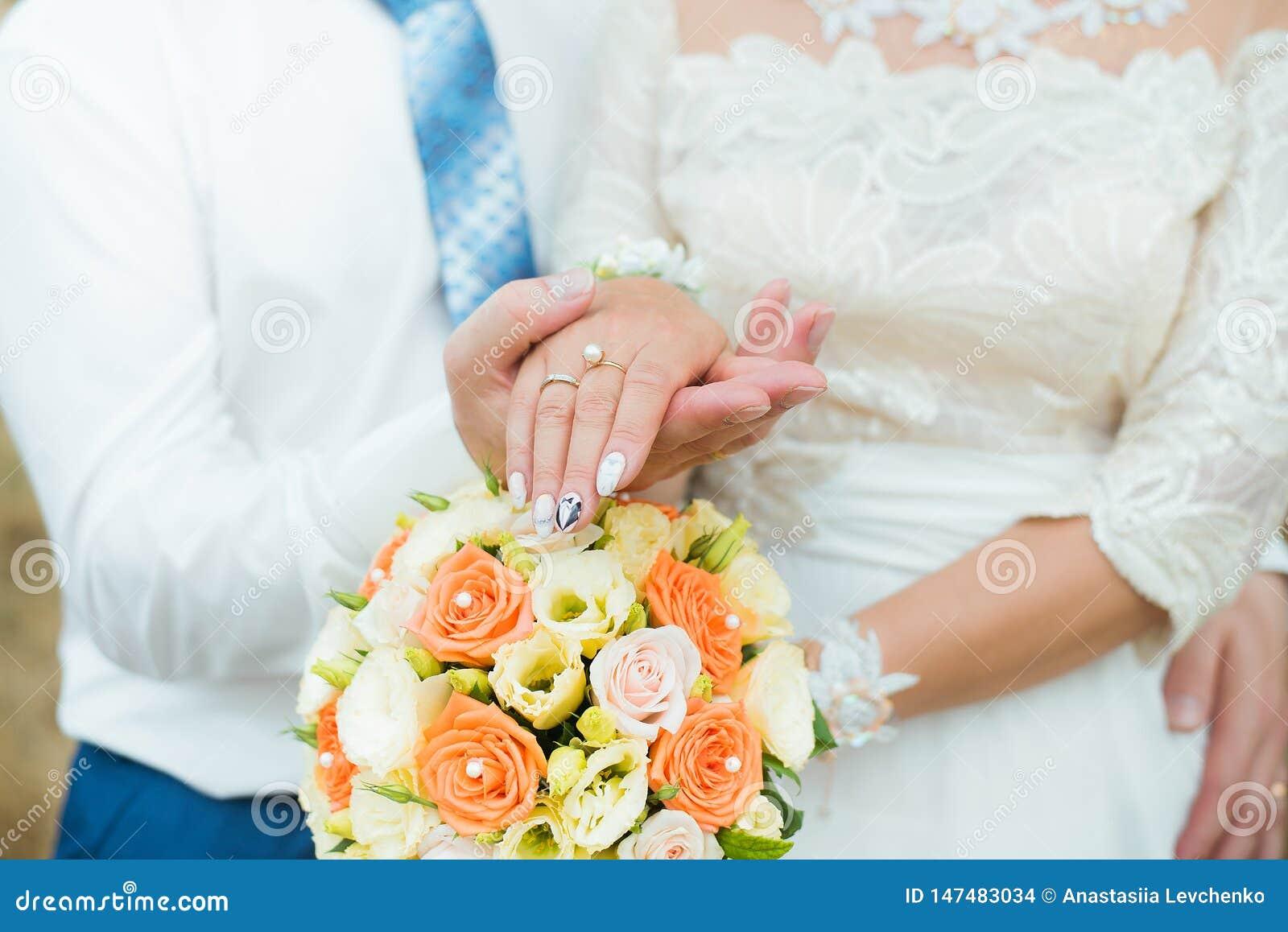 新郎和新娘的手有结婚戒指和花玫瑰的 爱和婚姻的概念