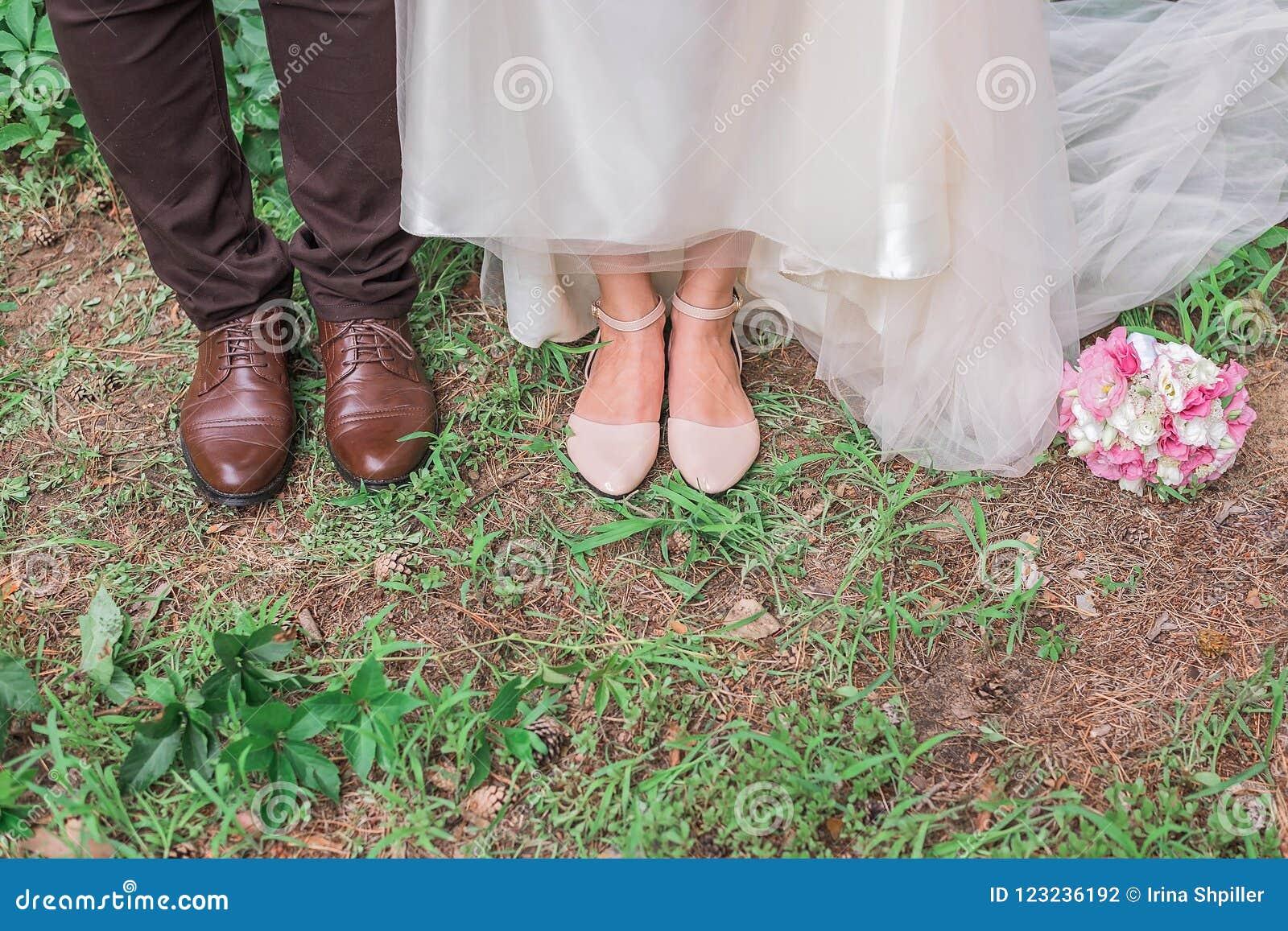 新郎` s和新娘` s的逗人喜爱的播种的图片在草一起穿上鞋子身分