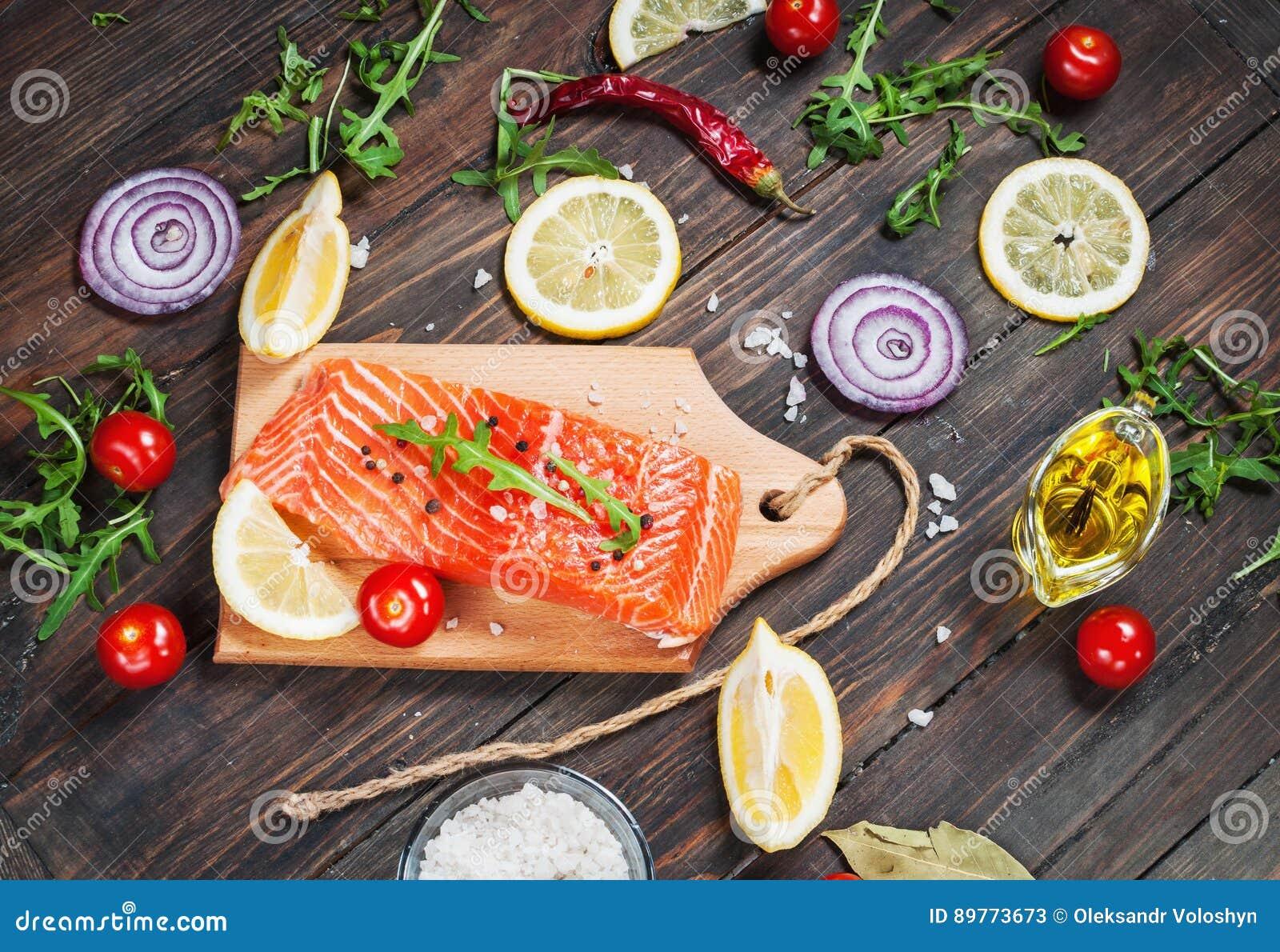 新鲜的三文鱼内圆角的可口部分用芳香草本、香料和菜-健康食物,饮食或烹调概念