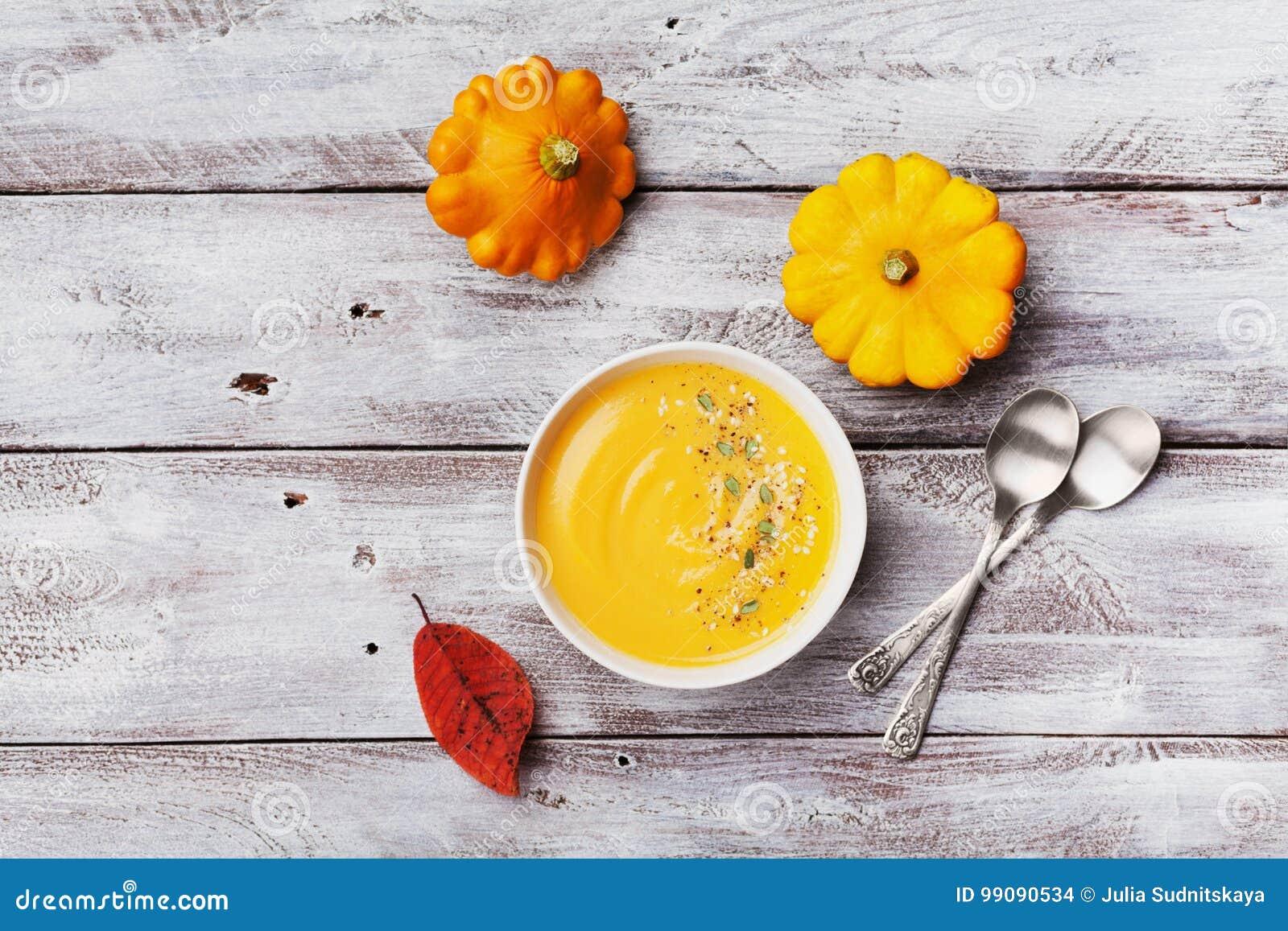 新鲜的南瓜汤装饰了种子和麝香草在白色碗在土气木台式视图 为秋天菜单射击的舒适生活方式