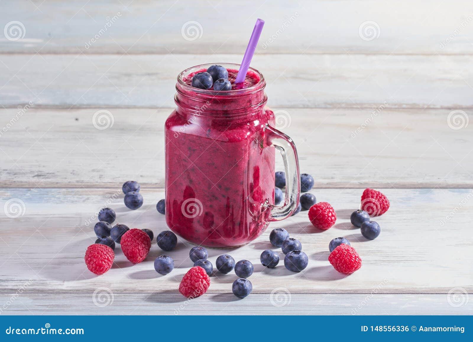 新鲜的圆滑的人用莓和蓝莓在一个玻璃瓶子在一张木白色桌上