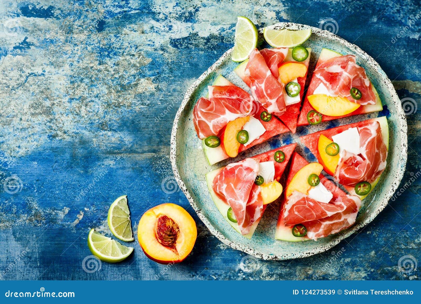 新鲜的夏天西瓜薄饼用希腊白软干酪,桃子、熏火腿、墨西哥胡椒和蜂蜜在蓝色背景下毛毛雨