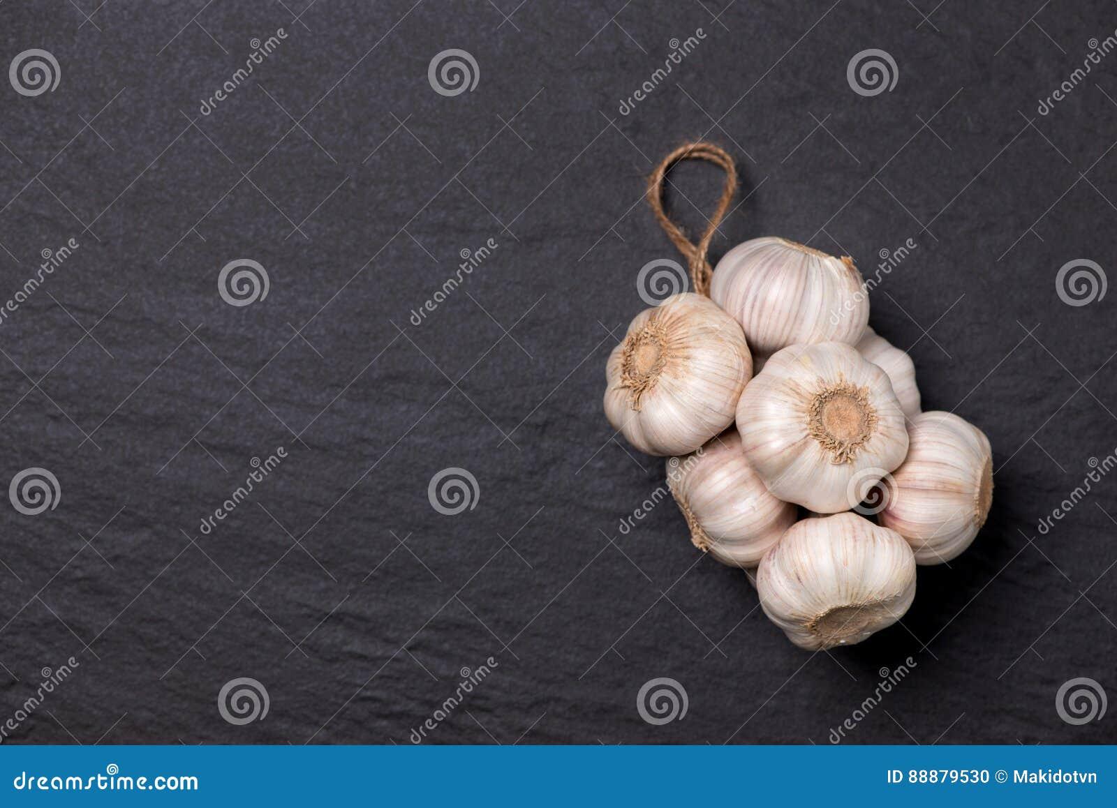 新鲜的大蒜 在黑石桌上的大蒜电灯泡