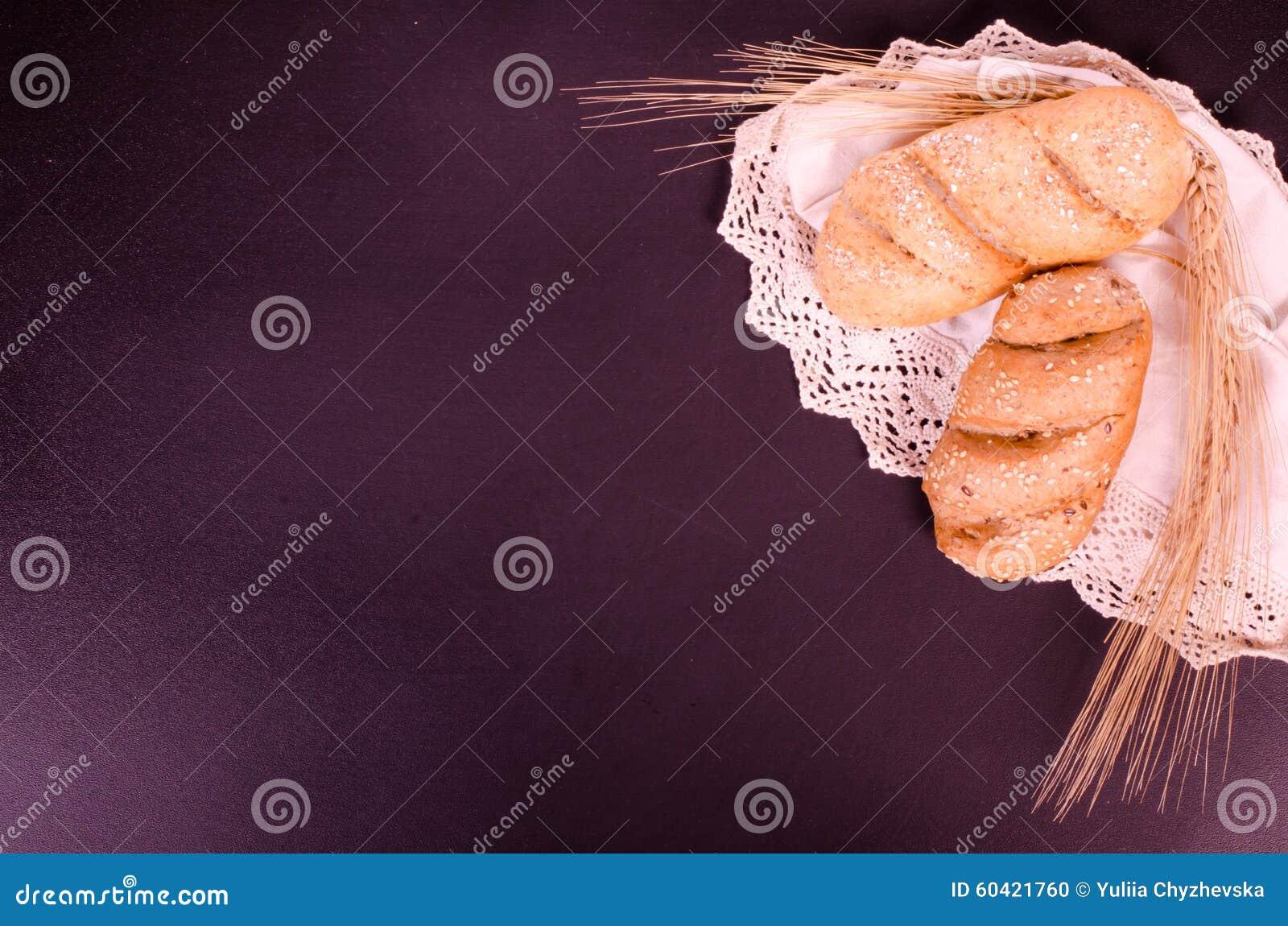 新鲜的小圆面包、鞋带和麦子耳朵在黑背景中