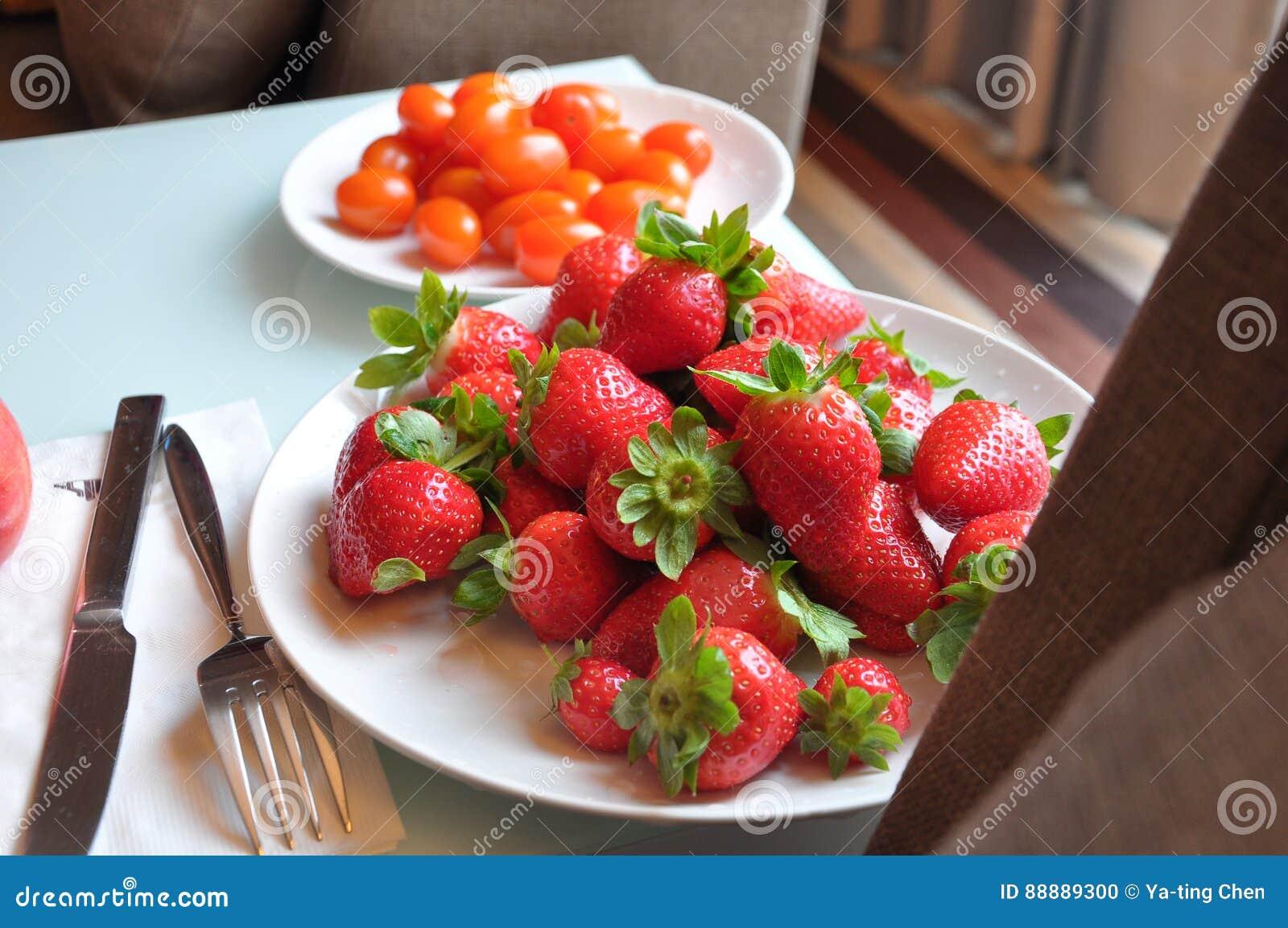 新鲜的草莓和西红柿板材在桌上在窗口附近