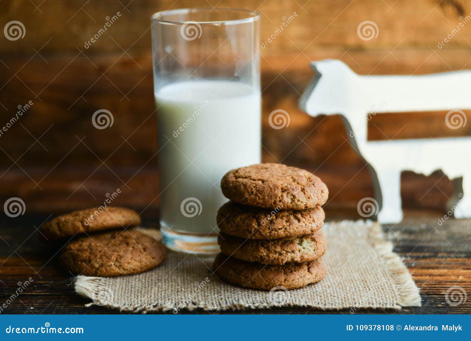 新鲜的麦甜饼和牛奶在木背景与燕麦钉
