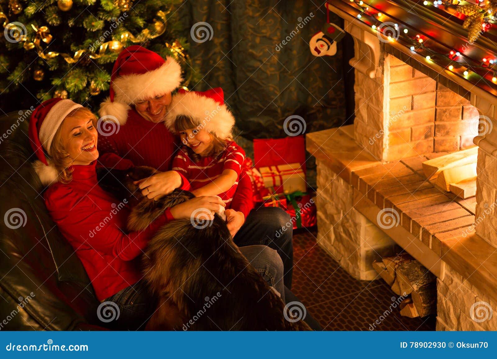新年好 使用与他们的狗的家庭在圣诞节欢乐装饰的客厅 宠物,人们,假日概念