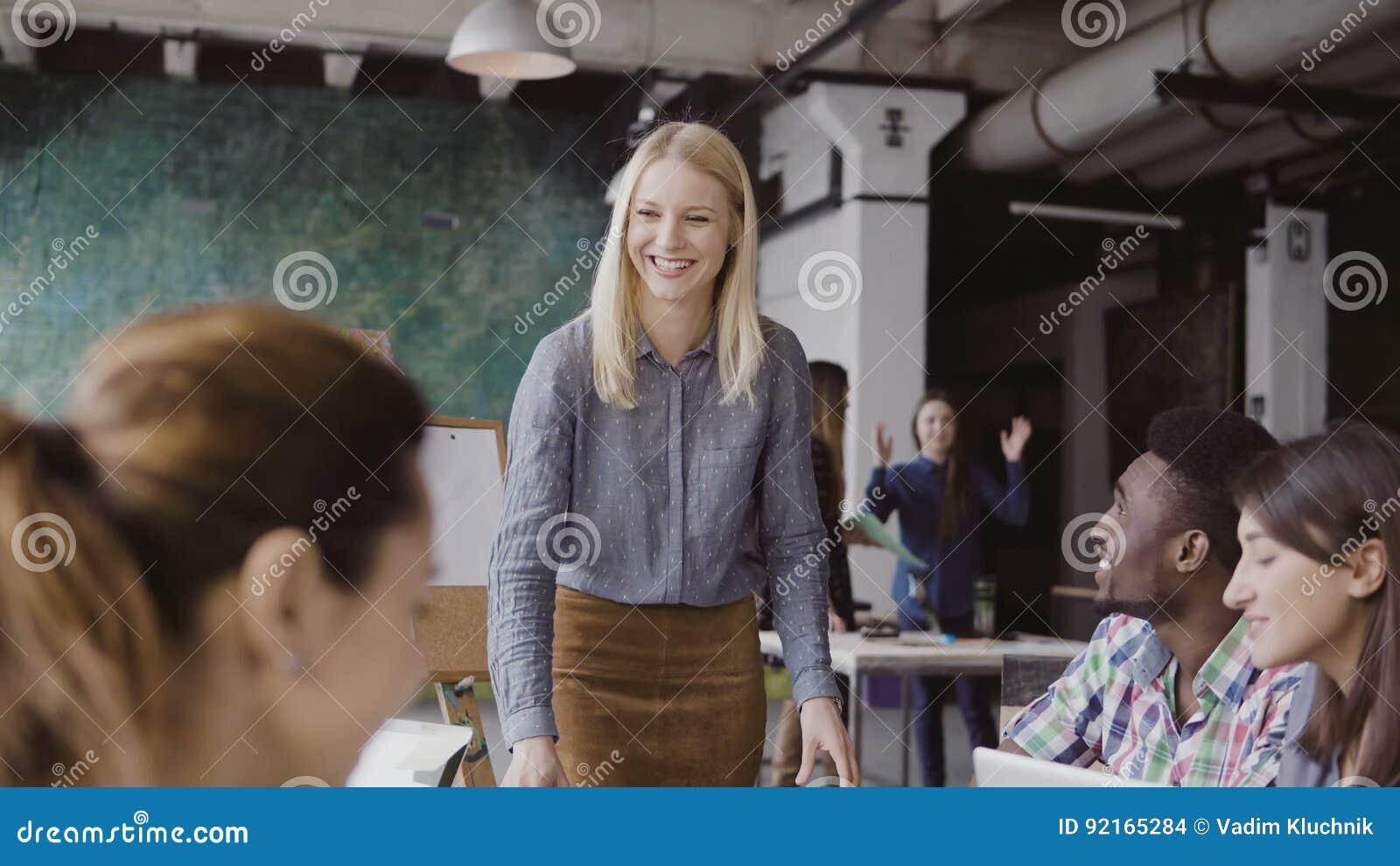 给方向的美丽的白肤金发的妇女经理不同种族的队 创造性的业务会议在现代行家办公室