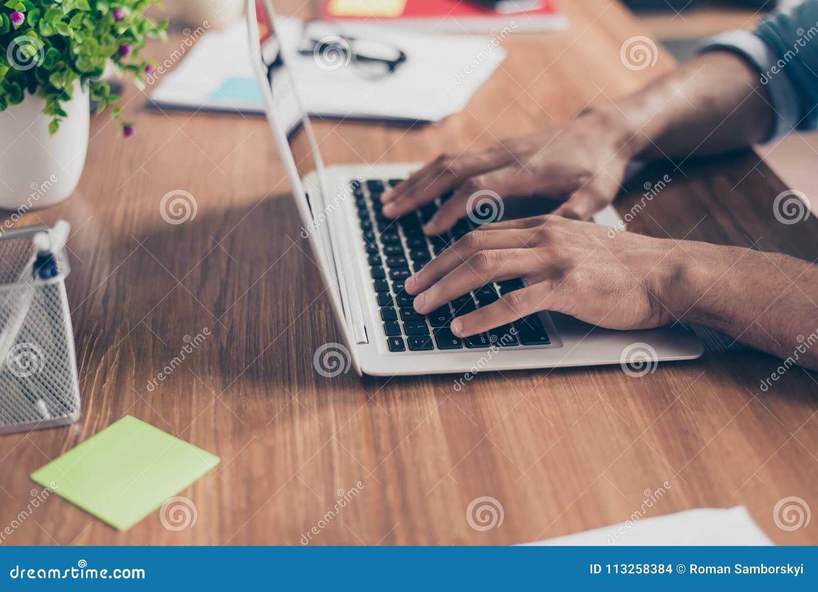 旁边外形播种了美国黑人的` s商人手照片在膝上型计算机键盘的在一个木桌面上的,繁忙键入数据