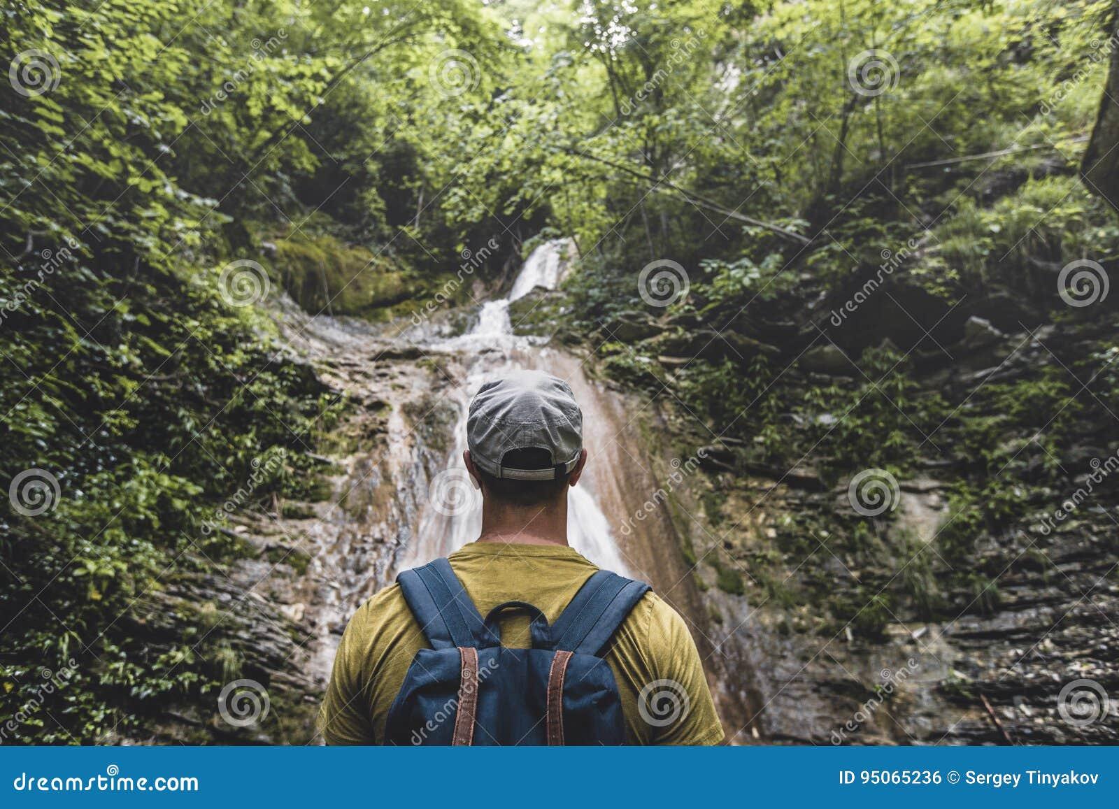 旅客到达了目的地和瀑布和秀丽享用视图未受破坏的自然 沉思冒险概念