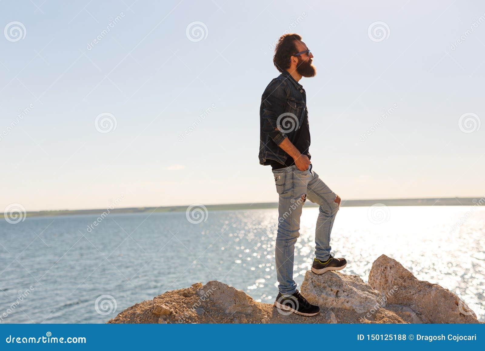 旅客在岩石反对美丽的海平安的波浪,摆在风平浪静附近的一个时髦的有胡子的行家男孩站立