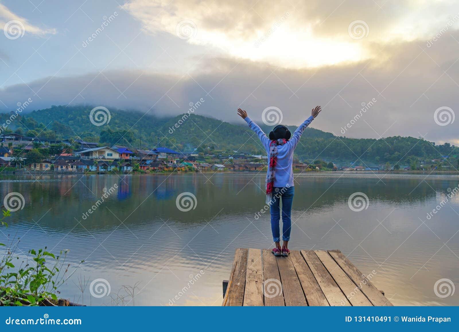 旅客感觉在桥梁的生活方式妇女战胜饰面在湖,季节冬天日出早晨,放松和