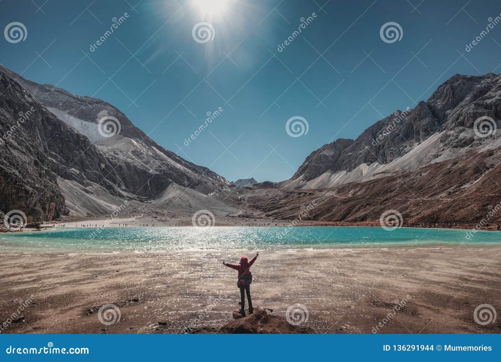 旅游培养手与绿松石湖和山脉在峰顶