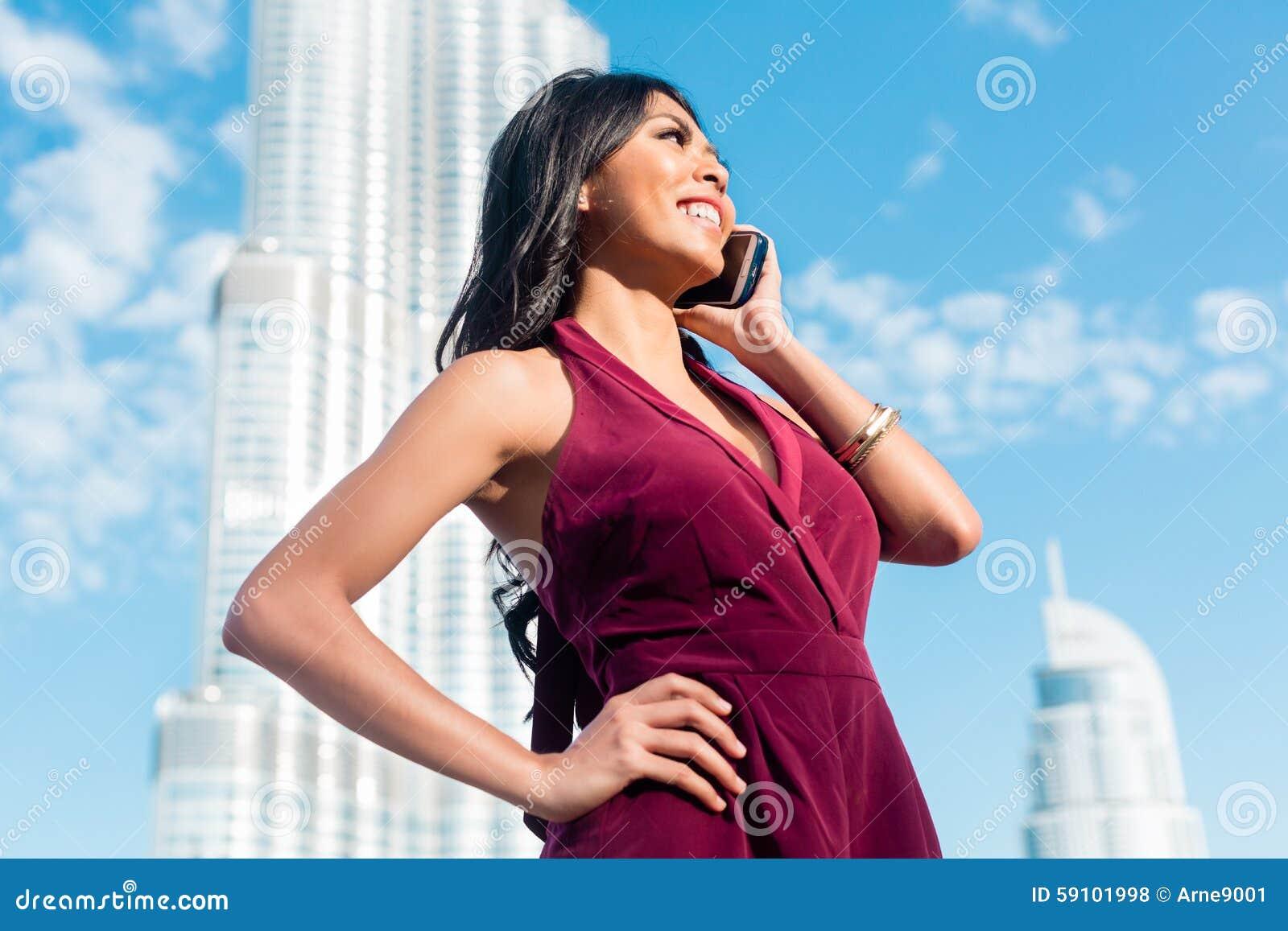 旅游妇女谈话在电话在迪拜